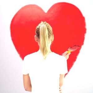 young woman painting a red heart on the wall